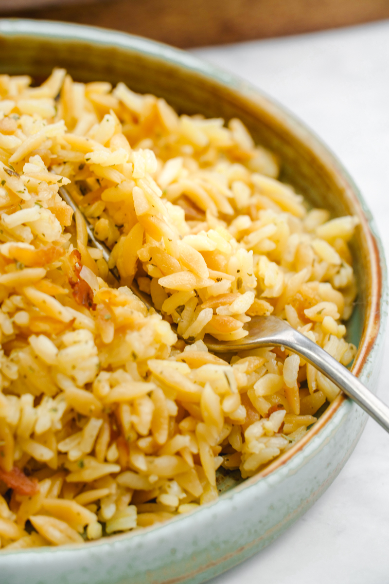 a bowl of rice pilaf being fluffed with a fork
