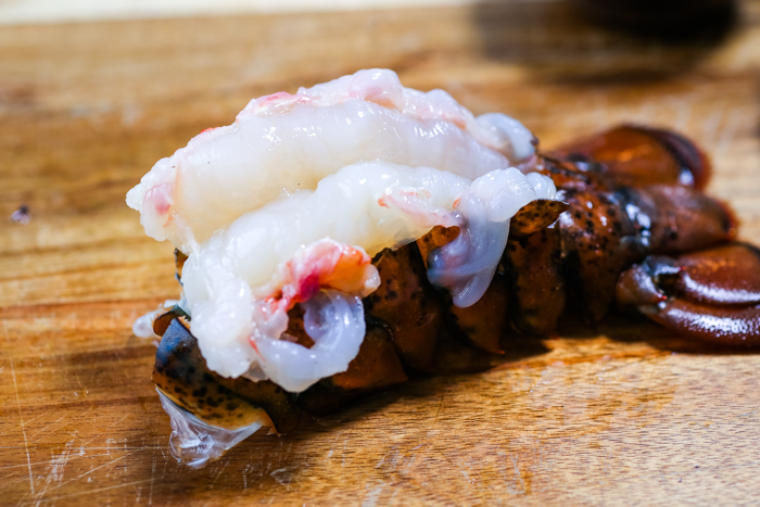 A butterflied lobster tail on a cutting board