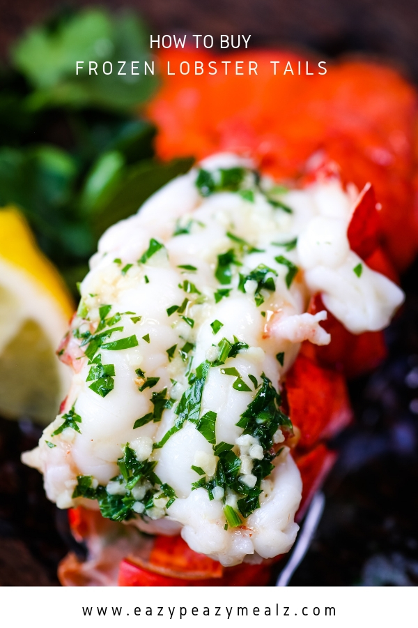 A cooked lobster tail covered with butter and garlic and parsley, next to a wedge of lemon