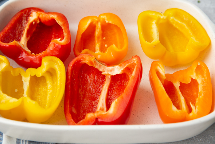 A baking pan with red, orange, and yellow pepper halves