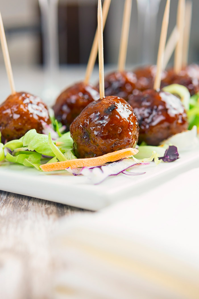 Delicious glazed meatballs on a serving tray atop a bed of greens.