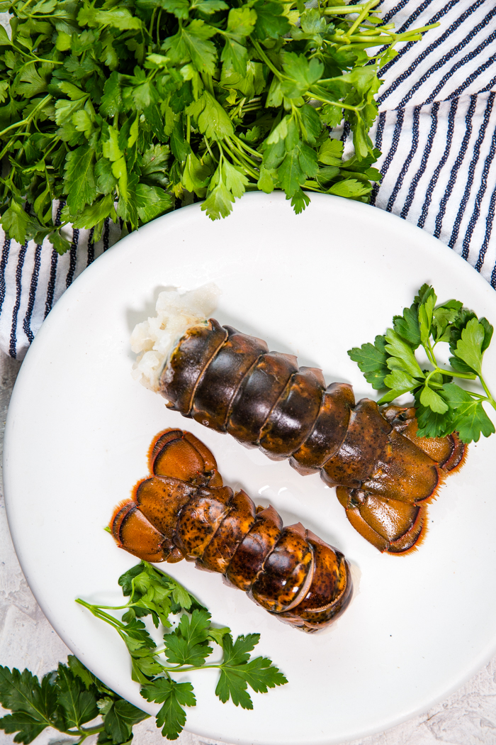 Two cold water lobster tails on a white plate.