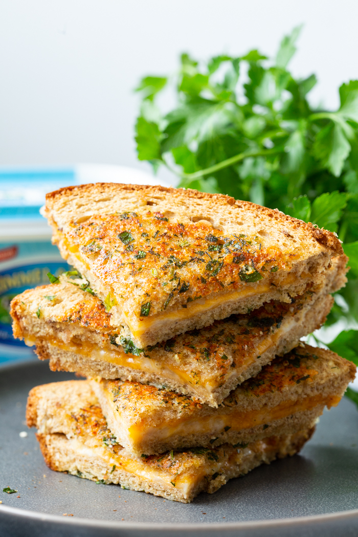 Garlic Parmesan Grilled Cheese sandwich cut into four pieces and stacked on a gray plate with parsley behind