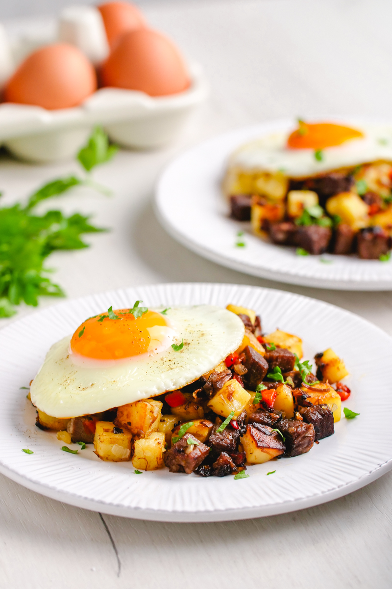 two plates topped with corned beef hash and an egg, garnished with parsley