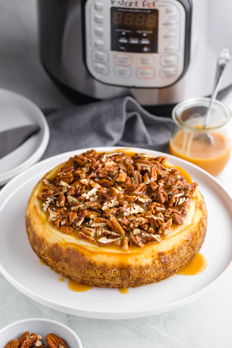 An instant pot cheesecake topped with caramel and pecans