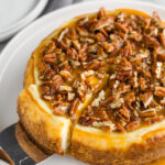 A whole instant pot cheesecake topped with caramel and pecans, with a slice cut and partially pulled out.