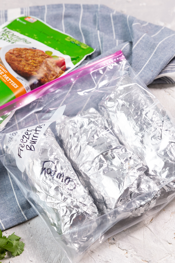 A bag with three freezer burritos and sausage patties in the background