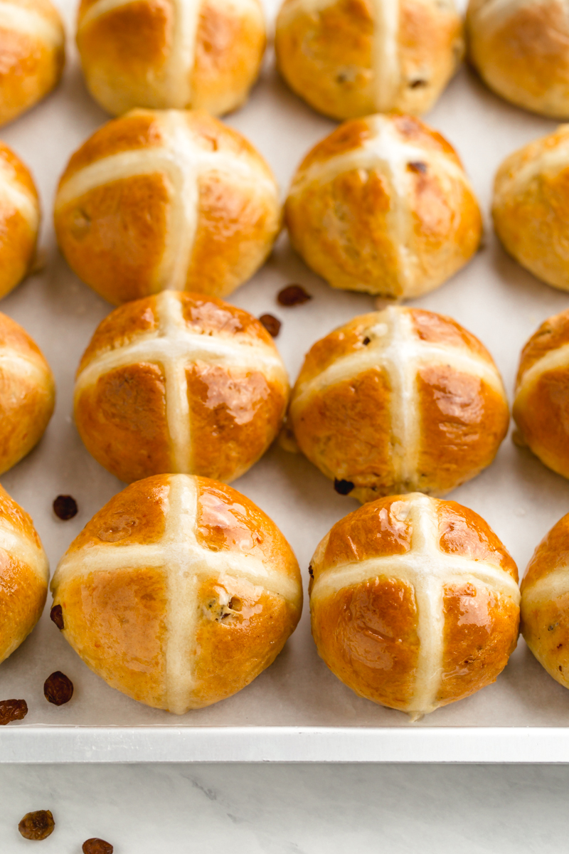 Hot crossed buns on a tray with the traditional cross on top