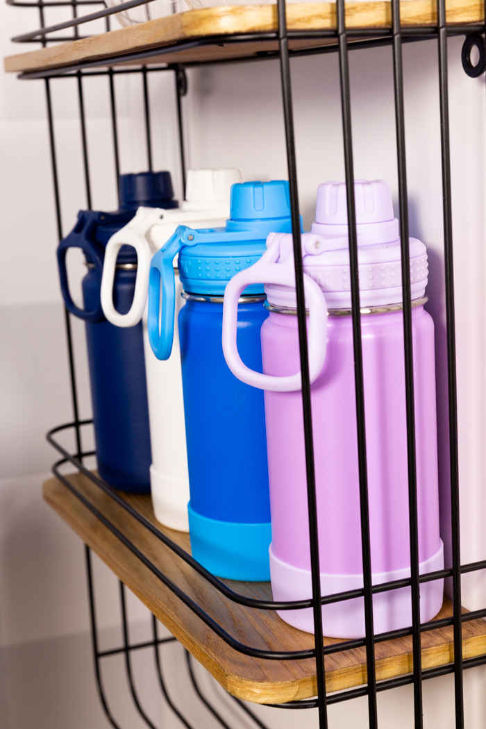 Water bottles on a shelf near the water dispenser