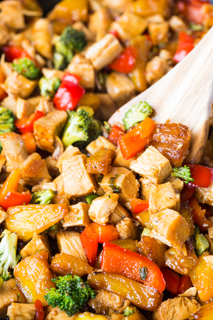 a close up of a spoonful of teriyaki chicken stir fry