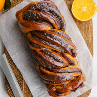 A top down look at a loaf of babka on top of a piece of parchment on a wooden cutting board. Knife next to the loaf. ORanges and chocolate garnish